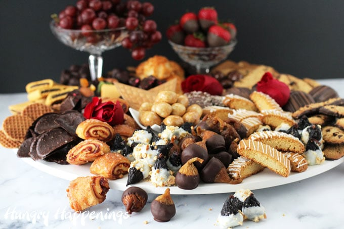 Artfully arrange chocolates, cookies, fruits, and nuts on a round platter to create a beautiful dessert charcuterie board.