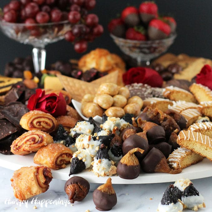 a beautiful display of desserts including chocolate dipped figs, cookies, fruit, and more