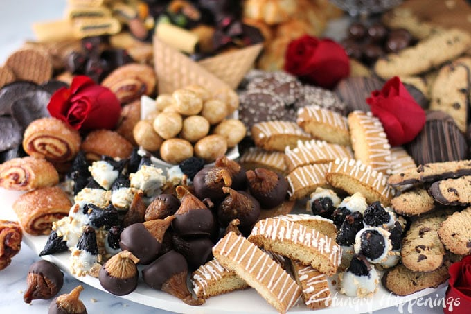 dessert board loaded with chocolate dipped figs, biscotti, chocolate dipped cookies, rugelach, truffles, coconut macaroons, and more