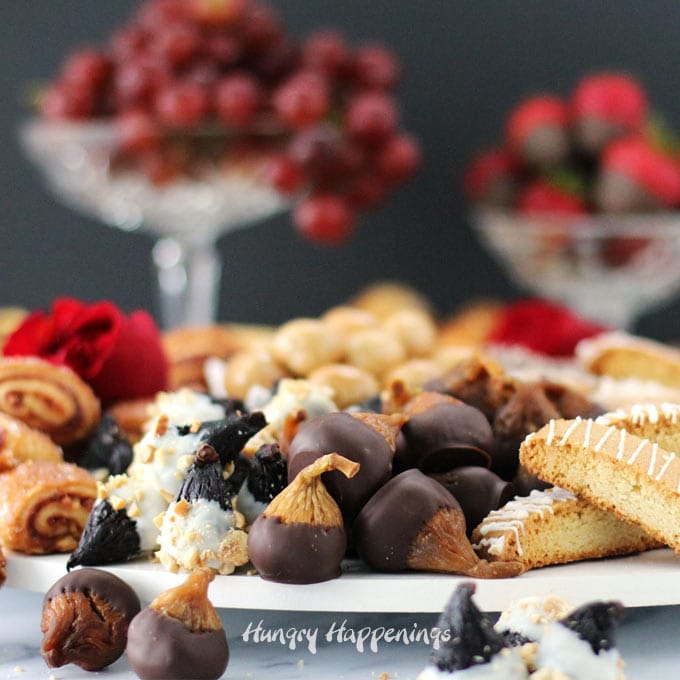 chocolate dipped figs, cookies, chocolates, red grapes, and chocolate dipped strawberries are arranged on a white platter to create a beautiful dessert board
