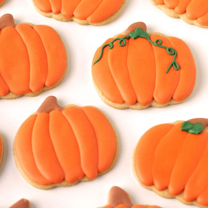 Pumpkin shaped pumpkin spiced cut-out cookies decorated with maple infused royal icing.