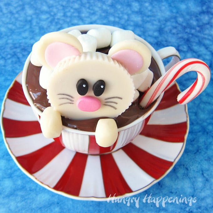 White Reese's Cup Mouse snuggled down into a hot chocolate cupcake with a candy cane stirrer all in red and white striped cup.