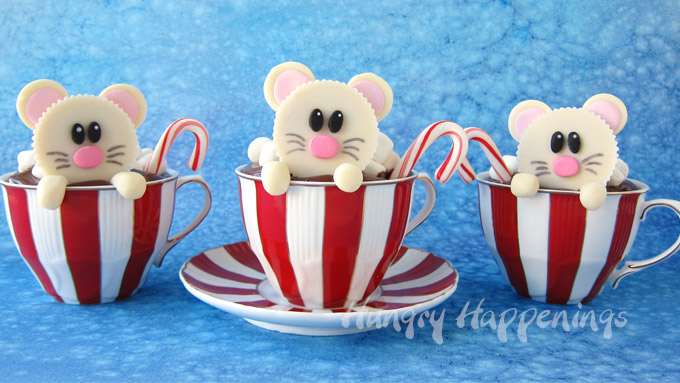 Reese's peanut butter cup mice popping out of Christmas teacups filled with hot cocoa cupcakes.