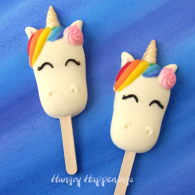 Colorful hand-painted white chocolate Unicorn Cakesicles filled with a blend of white cake and vanilla buttercream frosting.