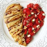 Chicken breast plated next to diced tomatoes, feta cheese, and basil to form a heart shape are drizzled with a balsamic glaze.