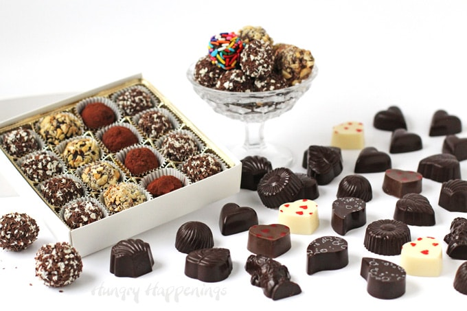 rolled chocolate truffles in a candy box and candy dish next to chocolate bon bons on a table