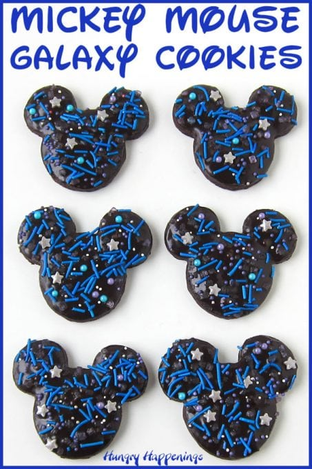 Chocolate Mickey Mouse Cookies glazed with shiny chocolate ganache and topped with blue jimmies, silver, purple, and white nonpareils, blue and purple sugar pearls, and silver star sprinkles.