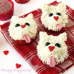 white puppy dog cupcakes with pink tongues and heart shaped noses next to raspberry cupcakes