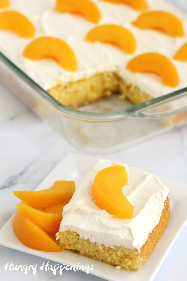 Eggless peach sheet cake topped with cream cheese frosting is cut and a piece is set on a small dessert plate and is topped with slice peaches.