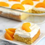 Slice of peach cake topped with cream cheese frosting and a slice of peach is set in front of the sheet cake.