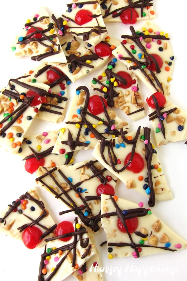 white chocolate bark topped with chopped peanuts, maraschino cherry halves, sprinkles, and hot fudge topping