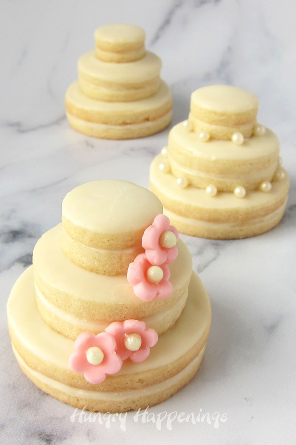 Stacked wedding cake cookies decorated with white chocolate, fondant flowers, or sugar pearls.