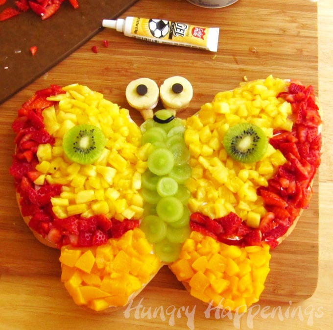 Use black gel to add a smile to the butterfly fruit pizza.