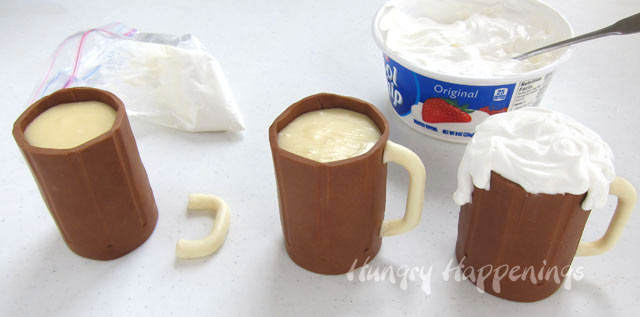 add a handle to each root beer mug cake then top with whipped cream foam