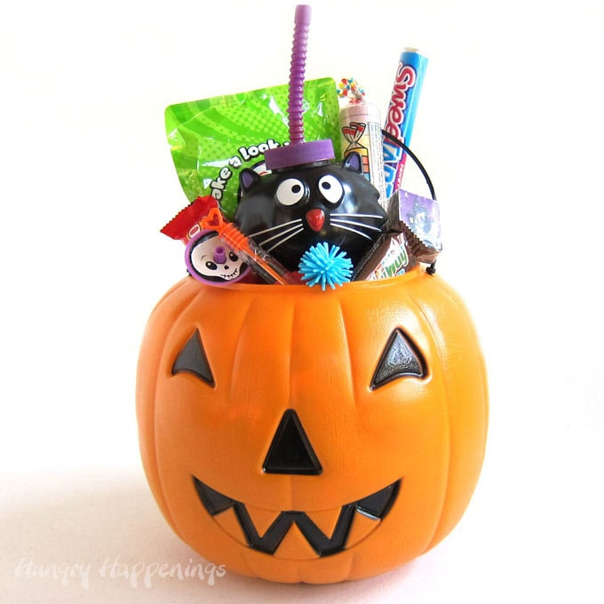 Plastic pumpkin pail filled with lots of Halloween candy and toys including bubbles, playing cards, and tops.