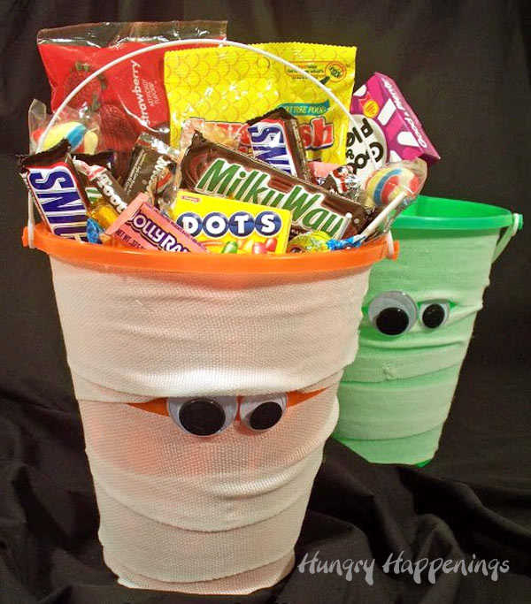 Beach pails decorated like Mummies for Halloween are filled with candy.