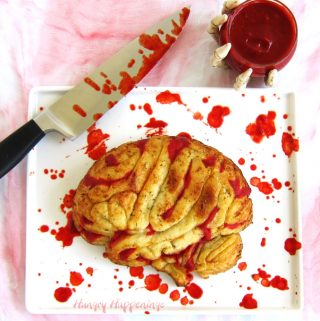 Stuffed Pizza Brain served with bloody marinara sauce on a blood stained white platter and a blood dripping knife.