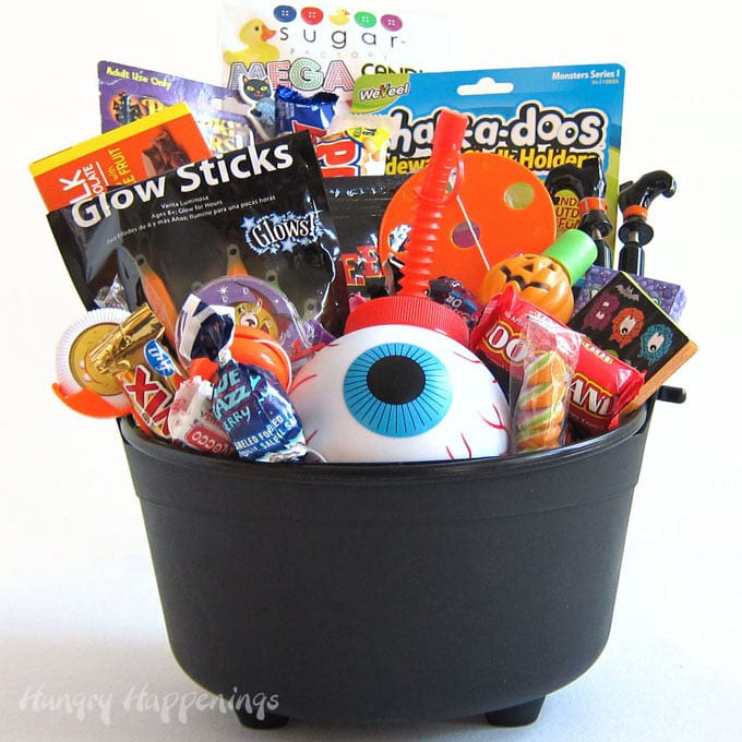 A plastic witch's cauldron filled with Halloween candy, toys, pumpkin carving tools, glow sticks, and an eyeball cup.