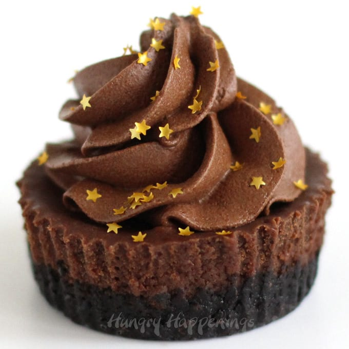 Mini chocolate cheesecake topped with a swirl of chocolate mousse and edible gold star glitter.