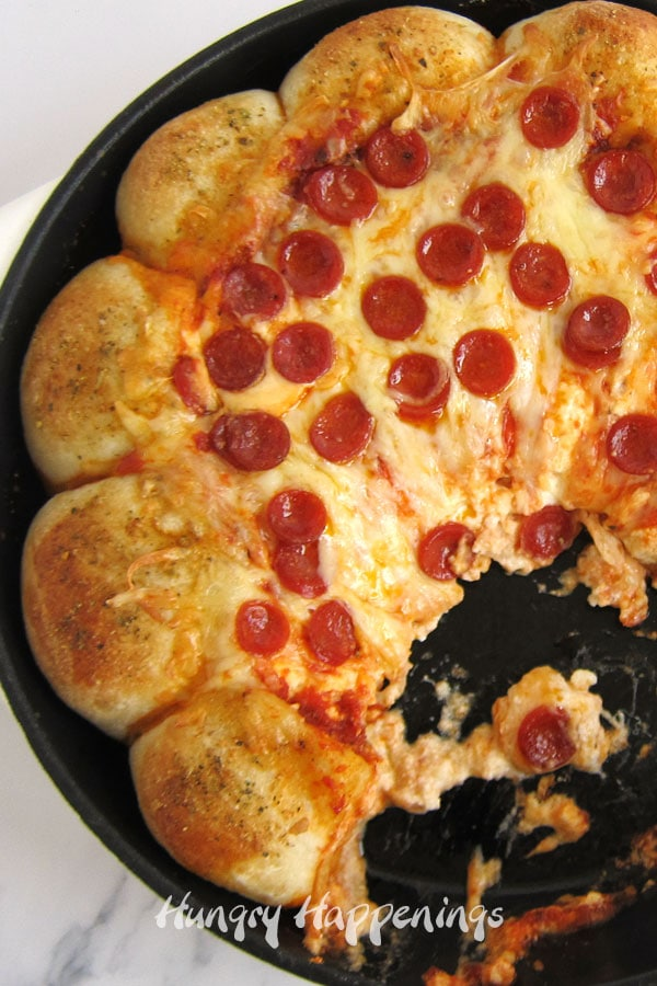 Pepperoni pizza dip baked in a cast-iron skillet is loaded with three kinds of cheese and lots of pepperoni.