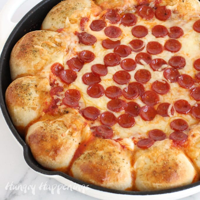 Pizza dip baked in a skillet surrounded by cheese-filled pizza crust topped with a sprinkling of parmesan cheese bread dip seasoning.