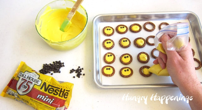Pipe yellow candy melts into pretzel rings then add two mini chocolate chip candy eyes to create smiley face pretzels.