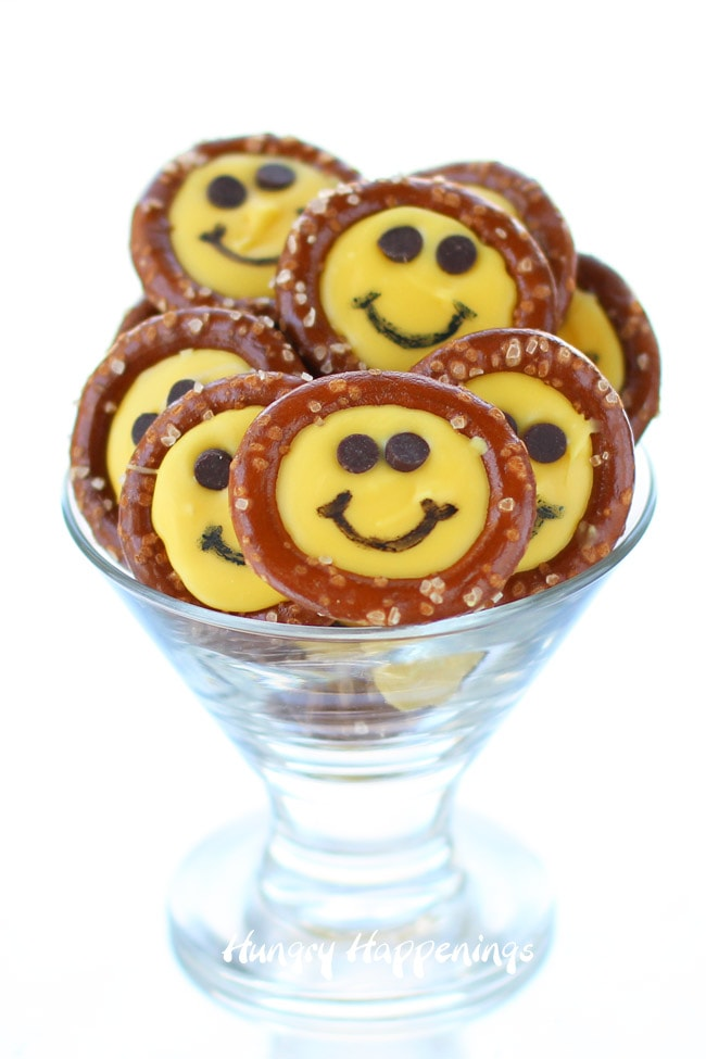 Smiley Face Pretzels - yellow-colored candy melt circles inside pretzel rings with chocolate chip eyes and a black food coloring smile