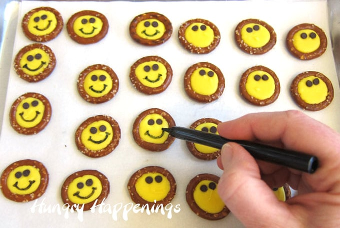 Use a black food coloring marker to draw a smiley onto the yellow candy melts.