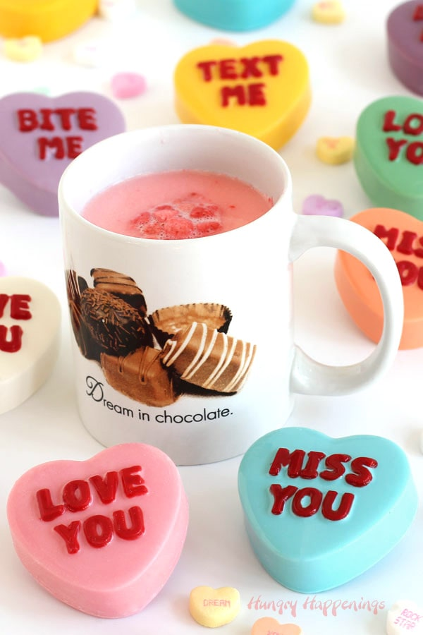 Conversation Heart Hot Chocolate Bombs around a mug of pink-colored white hot chocolate.
