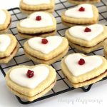 heart-shaped empire cookies are filled with raspberry preserves and are topped with a sweet glaze