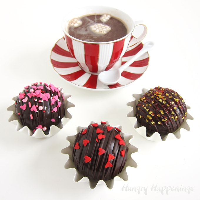 Round hot chocolate bombs topped with a drizzle of chocolate and Valentine's Day sprinkles melted in a mug of hot milk