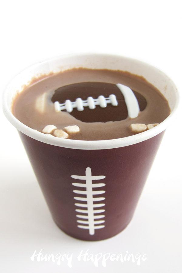 Football-shaped hot chocolate bomb melting into hot chocolate in a football paper cup