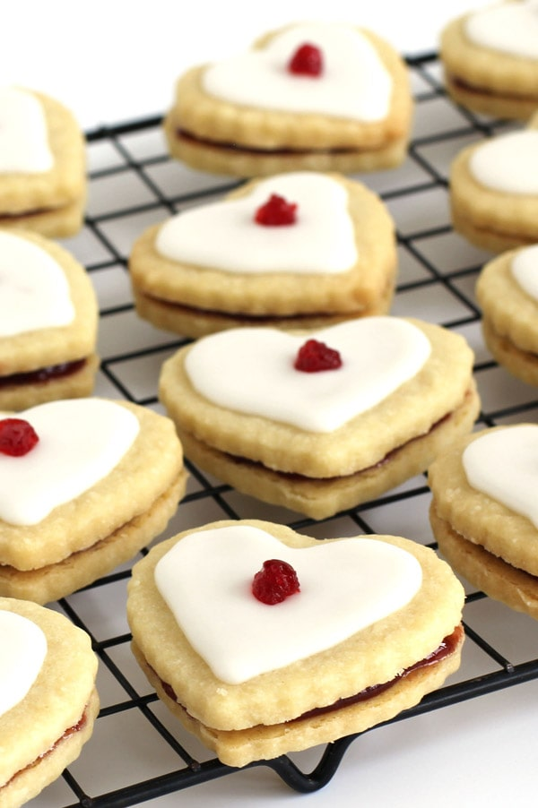 Valentine's Day Empire Cookie hearts filled with raspberry jam and topped with a sweet glaze and a glacee cherry