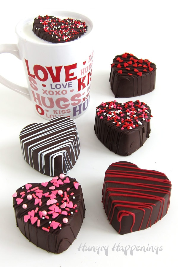 Heart-shaped hot chocolate bombs for Valentine's Day are decorated with a drizzle of chocolate and heart sprinkles
