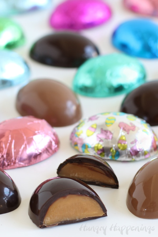 Caramel-filled chocolate eggs made in dark or milk chocolate are wrapped in colorful Easter foil candy wrappers.