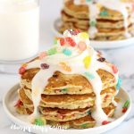 Cereal and Milk Pancakes made with Fruity Pebbles are topped with milk glaze and whipped cream.