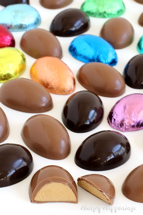 Peanut butter eggs for Easter made using milk chocolate or dark chocolate are wrapped in colorful foil candy wrappers.