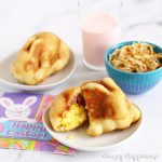 Easter breakfast pizza bunnies are filled with scrambled eggs, ham, and cheese and served with strawberry milk and hashbrowns.