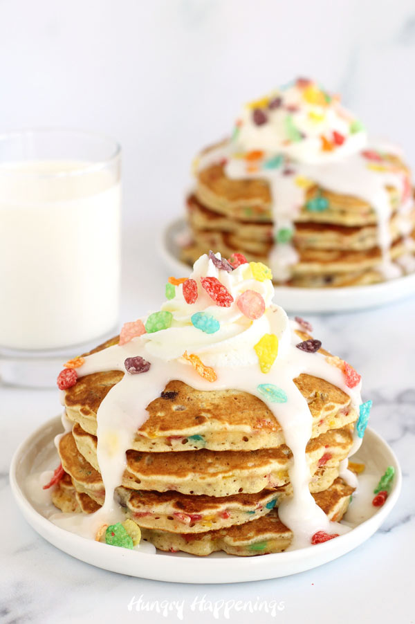 Fruity Pebbles Cereal and Milk Pancakes topped with whipped cream and milk glaze.
