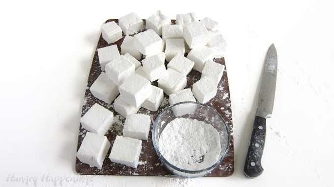 Cut homemade marshmallows using a buttered knife then dust the sticky sides with a blend of powdered sugar and corn starch.