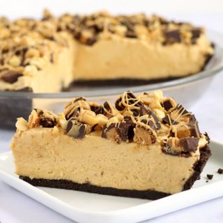 No-bake peanut butter pie on a chocolate cookie crust and topped with Reese's cups and peanuts.