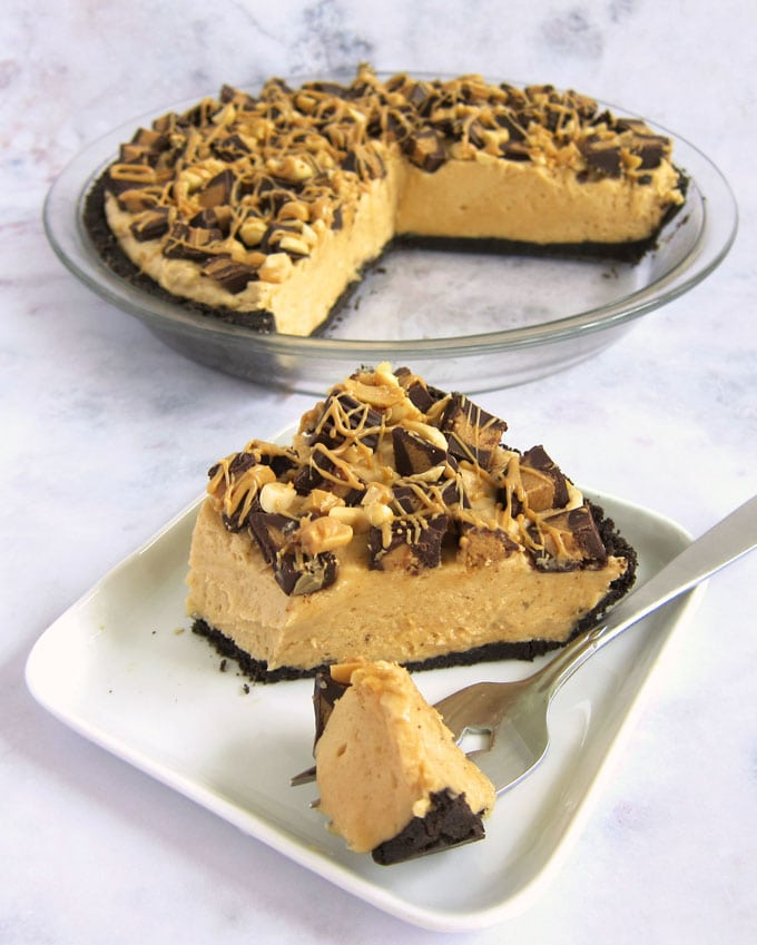 Creamy no-bake peanut butter pie topped with chopped Reese's Cups, peanuts, and peanut butter on an OREO Cookie crust.