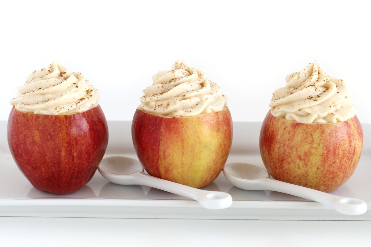 Apple Mousse served in hollow apples and sprinkled with cinnamon and nutmeg.