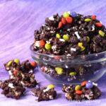 Dark chocolate Halloween popcorn topped with Halloween M&M's and bone sprinkles.