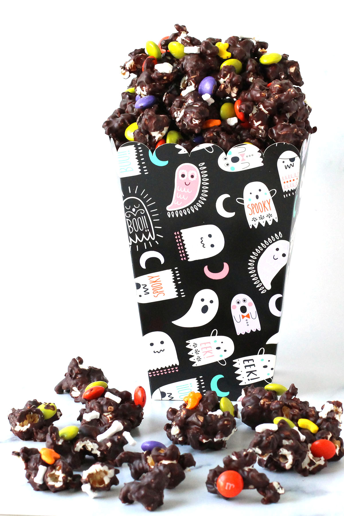 Halloween box filled with chocolate Halloween popcorn topped with M&M candies and Halloween sprinkles