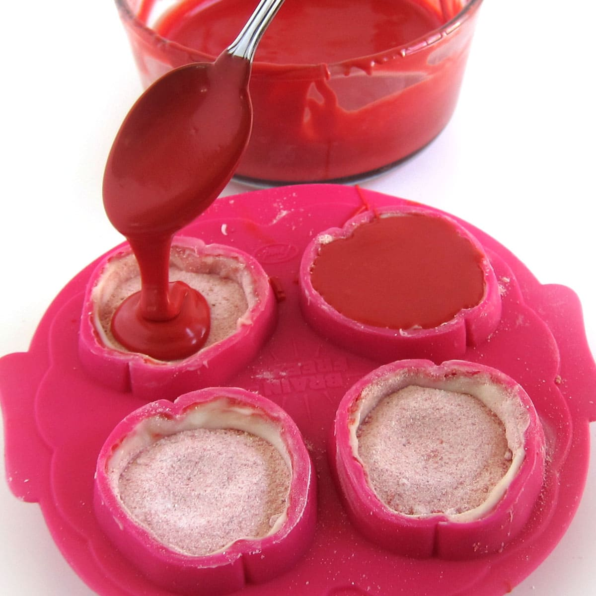 Spoon red candy melts over top of the strawberry hot cocoa mix in the brain mold.